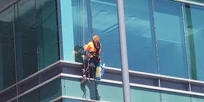 A window cleaner climbing out of a scaffold in Shanghai